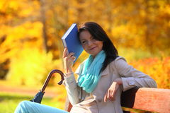 Girl relaxing in autumnal park. Fall season. Royalty Free Stock Photography