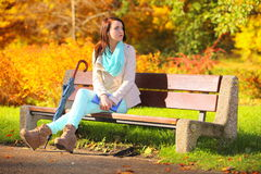 Girl relaxing in autumnal park. Fall season. Stock Photos