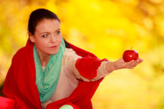 Girl relaxing in autumnal park holding red apple. Stock Images