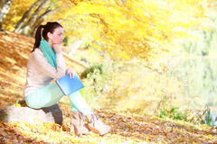 Girl relaxing in autumnal park reading book Stock Images