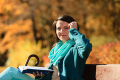 Girl relaxing in autumnal park reading book. Fall. Stock Image