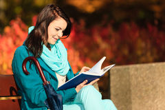 Girl relaxing in autumnal park reading book. Fall. Royalty Free Stock Photos
