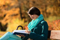 Girl relaxing in autumnal park reading book. Fall. Stock Photos