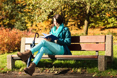 Girl relaxing in autumnal park reading book. Fall. Royalty Free Stock Photography