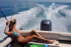 Girl relaxing on the back of motor boat. Cruising on speed at tropical water Stock Photo