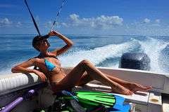 Girl relaxing on the back of motor boat. Cruising on speed at tropical water Stock Photography