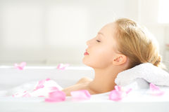 Girl relaxing in bathtub. On light background Stock Photos
