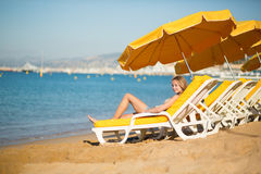 Girl relaxing on a beach chair near the sea Royalty Free Stock Photography