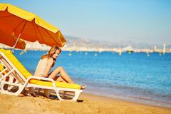 Girl relaxing on a beach chair near the sea Stock Photos