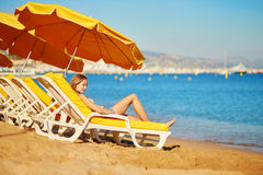 Girl relaxing on a beach chair near the sea Stock Images