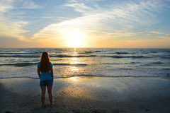 Girl relaxing on the beach at sunset. Stock Photos