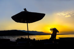 Girl relaxing on the beach under umbrella. Sunrise view at resort. Relaxing holiday landscape. Girl at chaise longue and parasol on beach silhouette Stock Image