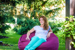 Girl relaxing in a bean bag chair on the green grass Royalty Free Stock Photos