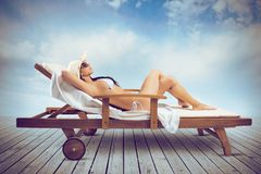 Girl relaxing. Beautiful girl relaxing on a deckchair in the beach Stock Photo