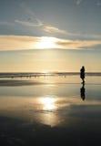 Girl relaxing on beautiful golden beach at sunrise. Stock Photos
