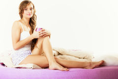 Girl relaxing on bed at morning with tea cup Royalty Free Stock Image