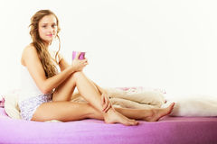 Girl relaxing on bed at morning with tea cup Royalty Free Stock Images