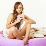 Girl relaxing on bed at morning with tea cup Stock Photos