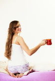 Girl relaxing on bed at morning with tea cup Royalty Free Stock Photos