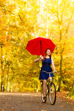 Girl relaxing with bicycle red umbrella in autumn park Stock Image