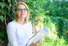 Girl relaxing with book green nature background. Literature as hobby. Girl keen on book keep reading. Bestseller top. List concept. Woman blonde take break stock images