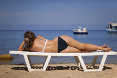 Girl relaxing in a chair on a beach. Thassos island in greece, focus is on the model Royalty Free Stock Photography