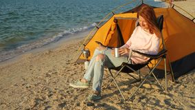 Girl relaxing in a chair. On a sandy beach near the hiking tent stock video footage