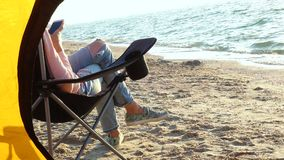 Girl relaxing in a chair. On a sandy beach near the hiking tent stock footage