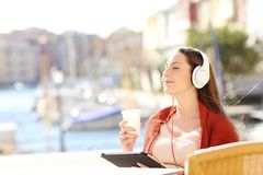 Girl relaxing in a coffee shop listening to music on vacation. Happy girl relaxing in a coffee shop listening to music with headphones and a tablet on vacation Royalty Free Stock Photos