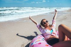 Girl relaxing on donut lilo on the beach. Playing with inflatable ring. Summer holiday idyllic on a tropical island Royalty Free Stock Photography