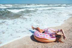 Girl relaxing on donut lilo on the beach. Playing with inflatable ring. Summer holiday idyllic on a tropical island Stock Images