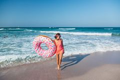 Girl with donut lilo on the beach. Girl relaxing with donut lilo on the beach. Playing with inflatable ring. Summer holiday idyllic on a tropical island Royalty Free Stock Image