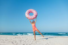 Girl with donut lilo on the beach. Girl relaxing with donut lilo on the beach. Playing with inflatable ring. Summer holiday idyllic on a tropical island Royalty Free Stock Photos
