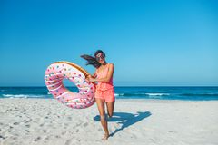 Girl with donut lilo on the beach. Girl relaxing with donut lilo on the beach. Playing with inflatable ring. Summer holiday idyllic on a tropical island Royalty Free Stock Photo
