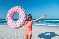 Girl with donut lilo on the beach. Girl relaxing with donut lilo on the beach. Playing with inflatable ring. Summer holiday idyllic on a tropical island Royalty Free Stock Photography