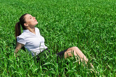 Girl relaxing on field Stock Image