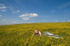 Girl relaxing among flowers. On a sunny day Stock Photos