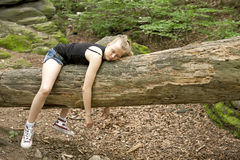 Girl relaxing in forest. Young girl relaxing on a tree trunk in a forest Royalty Free Stock Photography