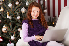 Girl relaxing in front of a Christmas tree Stock Image