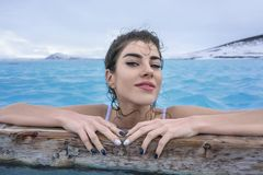 Girl relaxing in geothermal pool outdoors. Happy girl in a white swimsuit holds a wooden crossbeam in the geothermal pool on the background of snow mountains and Stock Photography