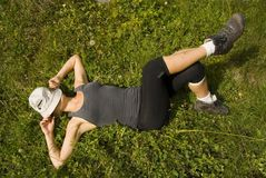 Girl relaxing on a grass. Beautiful girl takes a break during mountain hike royalty free stock image