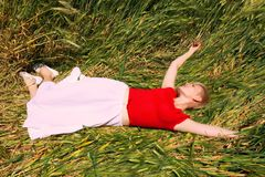 Girl relaxing in green field Stock Photo