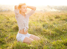 Girl is relaxing on green field. Beautiful girl is relaxing while sitting on green field Stock Photography