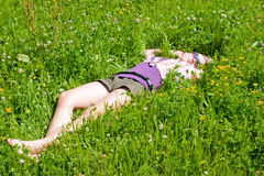 Girl relaxing in green meadow Royalty Free Stock Image