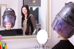 Girl relaxing with hairdryer by hairstylist in hair beauty salon. Mirror. Stock Photos