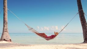 Girl relaxing in a hammock on tropical island beach. Summer vacation