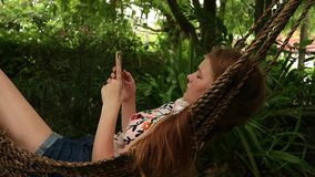Girl relaxing in hammock uses a smartphone, swaying gently near hotel on beach stock footage