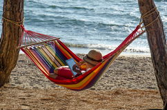 Girl relaxing on hammock and using digital tablet Stock Images
