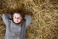 Girl relaxing on hay and thinking Royalty Free Stock Images