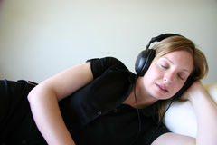 Girl relaxing with headphones and music. Girl in black dress wearing headphones Royalty Free Stock Photo
